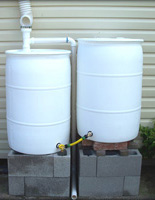 Two White Rain Barrels Connected on Concrete Block Stand